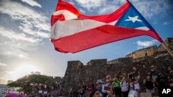 Demonstrators march against governor Ricardo Rosello, in San Juan, Puerto Rico, Wednesday, July 17, 2019. (AP Photo/Dennis M. Rivera Pichardo)