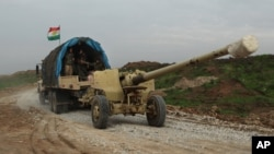 Iraqi Kurdish forces tow a howitzer near the front lines on their way to the city of Sinjar, Iraq, Dec. 19, 2014.
