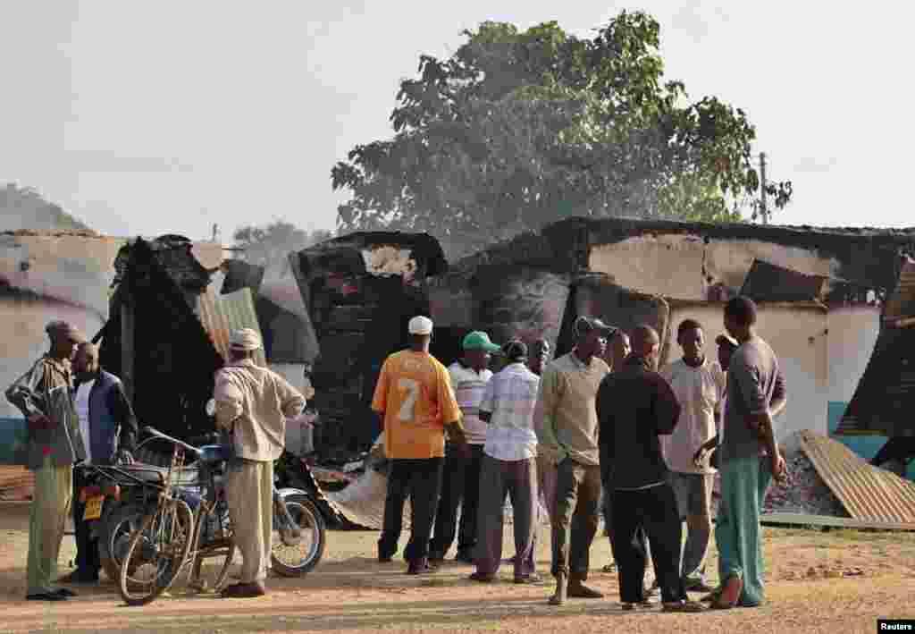 Mahalliy aholi vakillari Mpeketonida jangarilar vayron qilgan binolarni ko'zdan kechirmoqda, 16-iyun, 2014-yil.