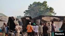 Residents gather behind destroyed structures after gunmen attacked Mpeketoni, Kenya, June 16, 2014.