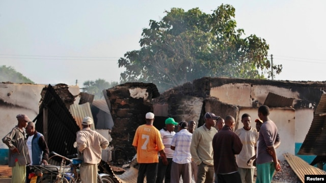 Residents gather behind destroyed structures after gunmen attacked Mpeketoni, Kenya, June 16, 2014.