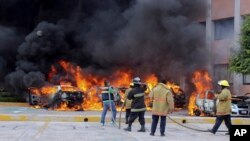 Firefighters try to extinguish burning vehicles in front of the state congress building after protesting teachers torched them in the state capital city of Chilpancingo, Mexico, Nov. 12, 2014.