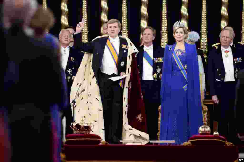 Dutch King Willem-Alexander raises his hand to take the oath by Queen Maxima and members of the royal household at his investiture in Nieuwe Kerk (New Church) in Amsterdam, the Netherlands.