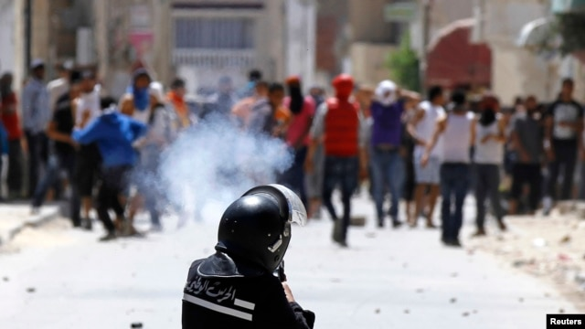 Riot officer fires teargas during clashes with supporters of Islamist group Ansar al-Sharia at Hai al Tadamon, Tunis, May 19, 2013.