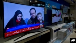 A Pakistani channel broadcasts a report about western couple, seen at a local electronic shop in Islamabad, Pakistan, Thursday, Oct. 12, 2017.