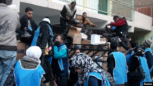 U.N. Relief and Works Agency (UNRWA) workers prepare aid parcels at the Palestinian refugee camp of Yarmouk, south of Damascus in this picture made available on February 26, 2014. World powers have passed a landmark Security Council resolution demanding a