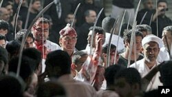 Bahraini men participates in a mourning procession with other Shiite men and boys, cutting their heads with the tips of swords to draw blood as they mark Ashura, the anniversary of the 7th century death of Imam Hussein, grandson of Islam's founding prophe