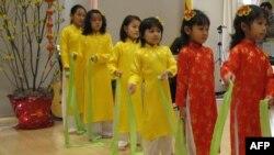 Các bé gái, xinh xắn trong chiếc áo dài truyền thống của người Việt Nam, trình diễn tại Hội chợ Tết
