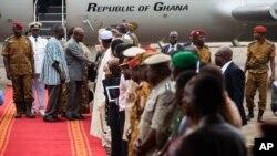 Le président du Ghana John Dramani Mahama, arrière centre, serrant la main des personnes venues l'accueillir à l'aéroport de Ouagadougou, au Burkina Faso, le mercredi 5 novembre 2014, avec à ses côtés le lieutenant-colonel Isaac Yacouba Zida, arrière gauche. (AP Photo / Theo Renaut)
