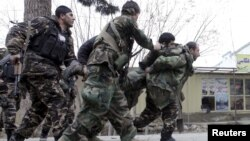 Pasukan keamanan Afghanistan menggendong rekannya yang terluka dalam baku tembak melawan kawanan bersenjata di Mazar-i-Sharif, Afghanistan, Senin (4/1).