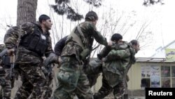4일 아프가니스탄 북부 마자리샤리프 주재 인도 영사관 주변에서 보안군과 무장괴한들 사이에 총격전이 벌어진 가운데, 보안군이 부상당한 동료를 부축하고 있다.