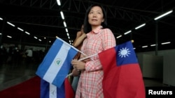 A Taiwanese citizen living in Managua holds Nicaragua's flag and Taiwan's flag as she waits for arrival of Tawain's President Tsai Ing-wen at the textile industrial park in Managua, Nicaragua Jan. 10, 2017.