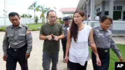 Singaporean journalist Lau Hon Meng, center left, and Malaysian journalist Mok Choy Lin, both accused of flying drones illegally over parliament buildings, are escorted at a court in Naypyitaw, Myanmar, Nov. 10, 2017.