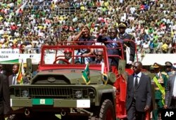 FILE - Zimbabwean President Robert Mugabe (C-R) and his wife Grace (C-L), greet the crowd as they arrive for his inauguration in Harare, Aug. 22, 2013.