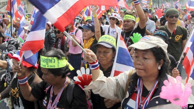 Anti-government protesters wave flags as they march on the street during a warm-up rally to paralyze the capital Tuesday, Jan. 7, 2014 in Bangkok, Thailand.