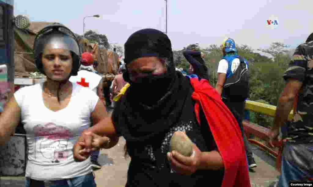 Una mujer sostiene una de las piedras que fueron utilizadas, por parte de los manifestantes en la frontera, en contra de la entrada de la ayuda humanitaria a Venezuela.