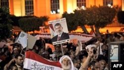 2013年7月31日在埃及首都開羅的反政府示威中,被推翻的總統穆爾西的支持群眾高舉穆爾西的照片和揮舞著國旗