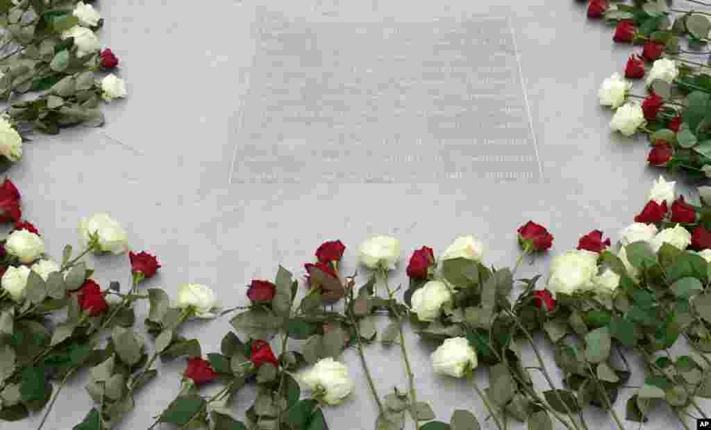 White and red roses are placed on a memorial at the former Nazi concentration camp Buchenwald near Weimar, Germany, to mark International Holocaust Day.