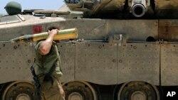 Binh sĩ Israel vác một vỏ xe tăng gần biên giới Israel và Gaza, ngày 24/7/2014.