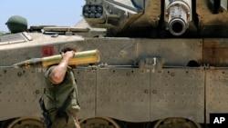 24일 이스라엘과 가자기구 국경에서 이스라엘 군인이 탱크에 실을 포탄을 나르고 있다.