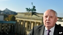 Former Soviet Leader Mikhail Gorbachev stands in front of the Brandenburg Gate in Berlin, Germany, Nov. 8, 2014.