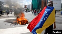 FILE - Protesters clash with riot police during a rally to demand a referendum to remove Venezuela's President Nicolas Maduro in Caracas, Venezuela.