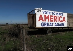 A Trump campaign sign is displayed near Los Banos, California, Dec. 16, 2016. A local farmer says Donald Trump's campaign vow to deport immigrants who are in the country illegally pushed him to buy more equipment, cutting the number of workers he'll need.