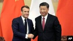 2019年11月6日,中国国家主席习近平和法国总统马克龙在人民大会堂举行联合记者会后握手.
