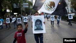 Demonstrators carry photos of 43 missing trainee teachers as a boy waves a Mexican flag, with its green and red parts replaced with black as a sign of mourning, during a march in support of the students in Mexico City, Dec. 6, 2014.