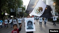 Demonstrator carries photograph of Alexander Mora Venancio, one of the 43 missing trainee teachers, during march in Mexico City Dec. 6, 2014.