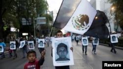 墨西哥的示威群眾手持失縱學生的相片走上街頭抗議。
