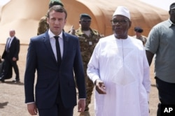 FILE - French President Emmanuel Macron, left, talks to Mali's President Ibrahim Boubacar Keita as they meet French soldiers of Operation Barkhane, France's largest overseas military operation, in Northern Mali, May 19, 2017.