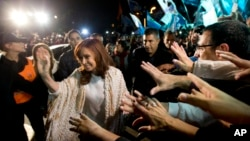 Former Argentina's President Cristina Fernandez, left, is greeted by followers upon her arrival at the airport in Buenos Aires, Argentina, April 11, 2016. After she spent four months in Patagonia, Fernandez' supporters gave her a hero's welcome at a Buenos Aires airport before she faces a court appearance over her possible role in an alleged scheme to manipulate the country's currency.