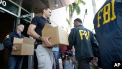 Petugas Biro Penyelidik Federal AS (FBI) mengumpulkan barang bukti skandal korupsi FIFA dari markas Konfederasi Asosiasi Sepak Bola Amerika Utara, Amerika Tengah dan Karibia (CONCACAF) di Miami Beach, Florida (27/5).