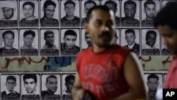 Asian workers walk past images of political prisoners plastered on a wall in Malkiya village, Bahrain, Nov. 4, 2015. Bahrain says it has arrested 47 suspects and seized explosives in a counter terrorism operation, and has again alleged Iranian involvement in militant attacks.