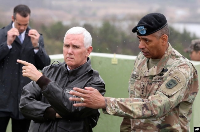 U.S. Vice President Mike Pence, left, is briefed by U.S. Gen. Vincent Brooks, right, commander of the United Nations Command, U.S. Forces Korea and Combined Forces Command from Observation Post Ouellette in the Demilitarized Zone (DMZ), near the border village of Panmunjom, South Korea, April 17, 2017.