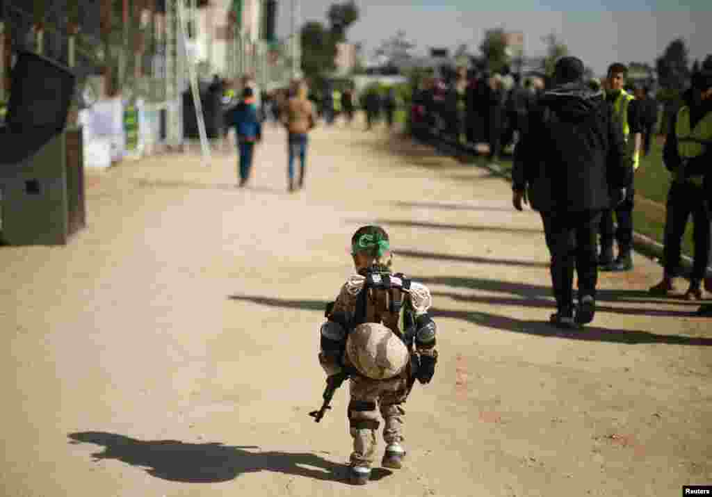 A Palestinian boy wearing a military costume arrives at a military-style graduation ceremony for youths who were trained at one of the Hamas-run Liberation Camps, in Gaza City.