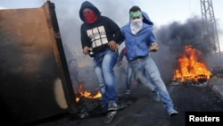 Palestinian protesters run for cover during clashes with Israeli troops near the Jewish settlement of Beit El, near the West Bank city of Ramallah, Oct. 9, 2015.