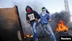 巴勒斯坦抗议者在西岸城市拉姆拉附近的一个犹太人定居点附近与以色列军人发生冲突期间寻求躲避场所(2015年10月9日)
