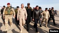 Iraq's Defence Minister Khaled al-Obeidi (2nd L) arrives at Base Speicher in the Iraqi city of Tikrit, Dec. 8, 2014.