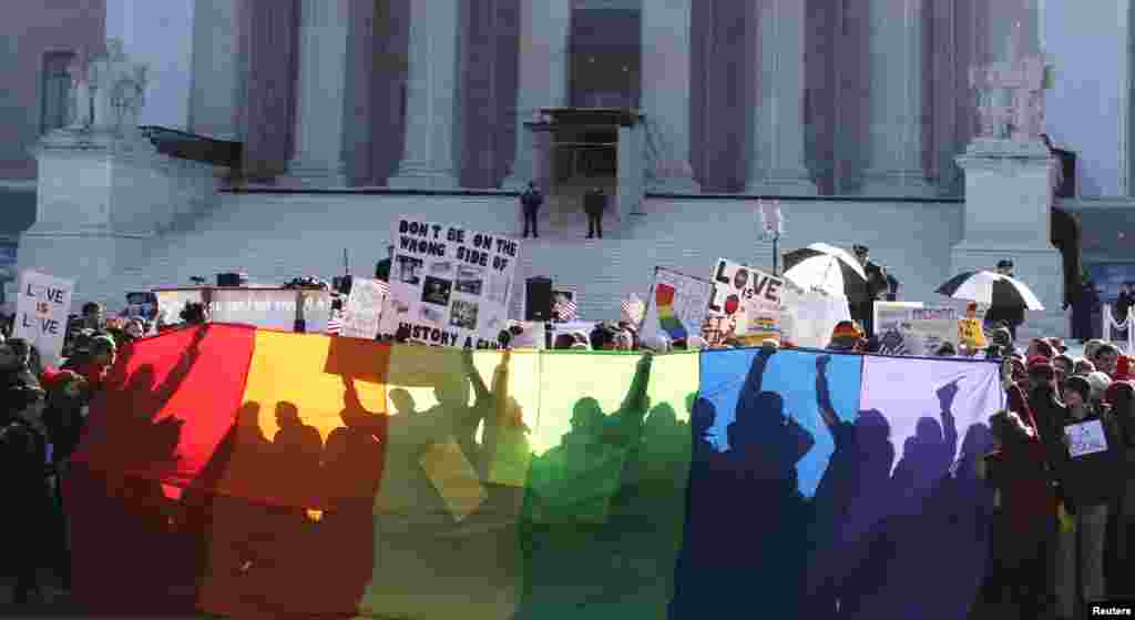 Anti-Proposition 8 protesters are shadowed by a rainbow banner in front of the U.S. Supreme Court in Washington, March 26, 2013.