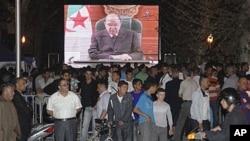 People congregate around a large TV screen showing Algeria's President Abdelaziz Bouteflika in Algiers, April 15, 2011