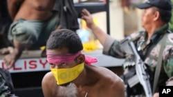 ຜູ້ຕ້ອງສົງໄສ ເປັນກະບົດມຸສລິມ ທີ່ທະຫານເວົ້າວ່າ ຖືກຈັບໄດ້ ຫລືບໍ່ກໍຍອມຈຳນົນ ຖືກສົ່ງໂຕໄປໃຫ້ການ ຢູ່ປ້ອມຕຳຫຼວດ ທີ່ເມືອງ Zamboanga ໃນພາກໃຕ້ຟີລິນ (26 ກັນຍາ 2013)