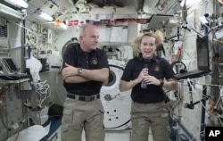 In this image made from video provided by NASA, astronaut Kate Rubins, right, speaks during an interview aboard the International Space Station on July 13, 2016.