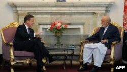 Britains' Prime Minister David Cameron (L) gestures during a meeting with Afghan President Hamid Karzai (R) at The Presidential Palace in Kabul, July 19, 2012.