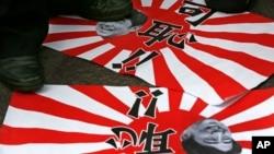 Poster anti-Jepang bergambarkan PM Shinzo Ane dan bendera militer Jepang nampak diinjak-injak masa dalam protes di Hong Kong (15/8). Ziarah dua menteri Jepang ke Yasukuni untuk menghormati tentara perang Jepang, kembali memicu kemarahan Korea Selatan dan Cina, dua dari korban agresi Jepang dalam paruh pertama abad ke-20.