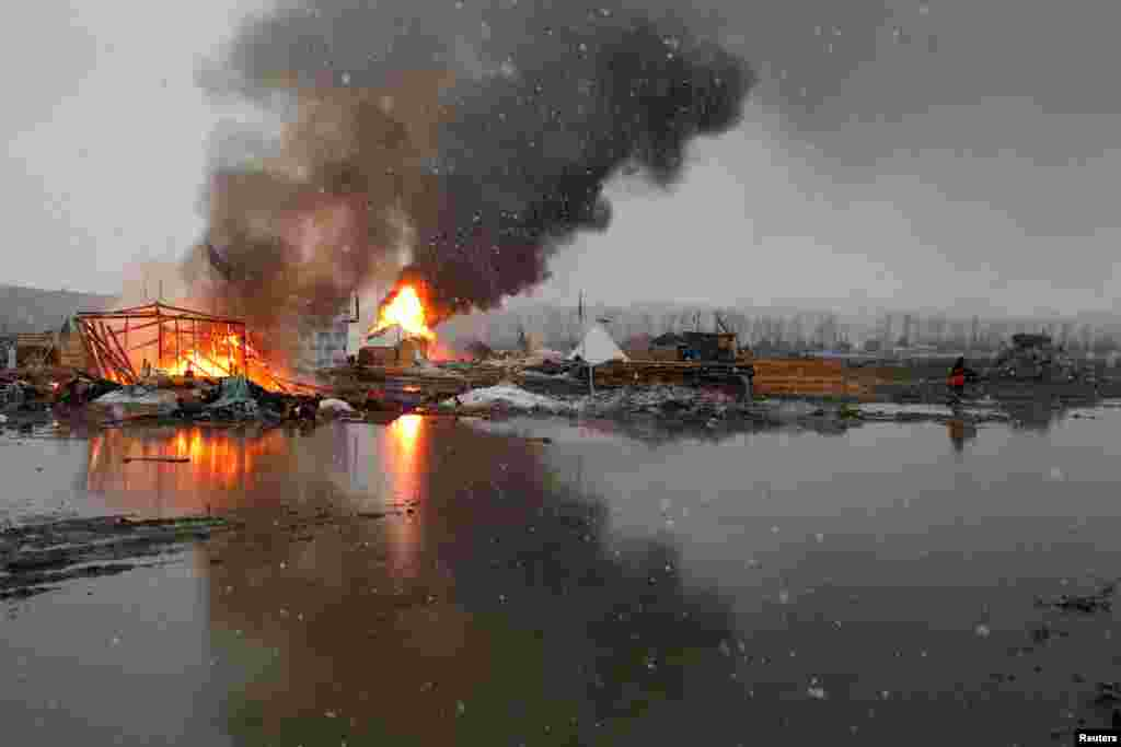 Buildings burn after being set on fire by protesters preparing to evacuate the main opposition camp against the Dakota Access oil pipeline, near Cannon Ball, North Dakota.
