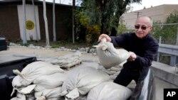 Frank Salazar, de Glendora, California, prepara bolsas de arena para proteger su vivienda de las posibles inundaciones que se prevén en los próximos días.