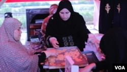 After the biscuits cool, women fill boxes which they distribute among protesters and neighbors that support their cause. (H. Elrasam/VOA)