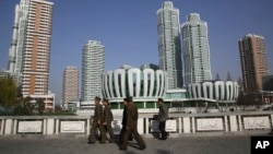 North Koreans walk past Ryomyong Street, the newest residential development in Pyongyang, North Korea, April 11, 2017. North Korea will mark the 105th anniversary of the birth of late leader Kim Il Sung on April 15.